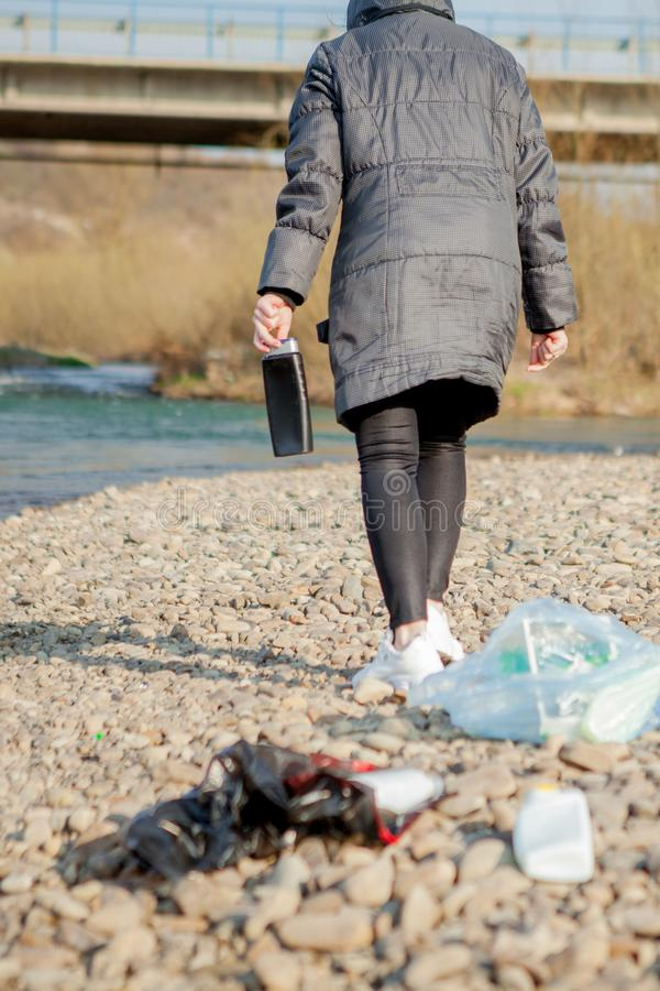 Νέα γυναίκα που συλλέγει τα πλαστικά απορρίμματα από την παραλία και που βάζει τα στις μαύρες πλαστικές τσάντες για ανακύκλωσης Κ στοκ εικόνες