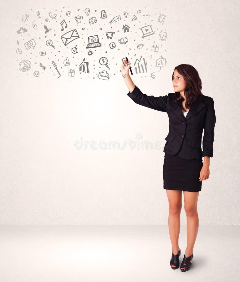 Νέα γυναίκα που σύρει και που σκιαγραφεί τα εικονίδια και τα σύμβολα στοκ φωτογραφία με δικαίωμα ελεύθερης χρήσης