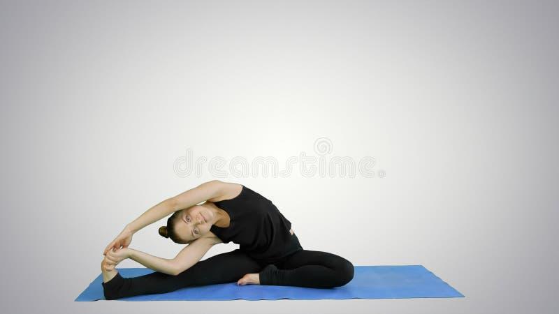 Νέα γυναίκα που τεντώνει τα πόδια της κάνοντας την πρακτική γιόγκας στο άσπρο υπόβαθρο στοκ φωτογραφία με δικαίωμα ελεύθερης χρήσης