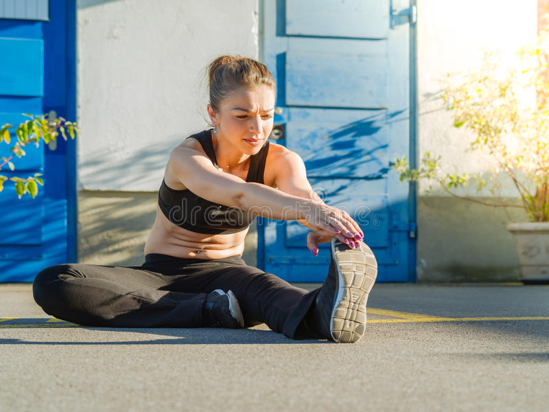 Νέα γυναίκα που τεντώνει τα πόδια της υπαίθρια στοκ φωτογραφίες
