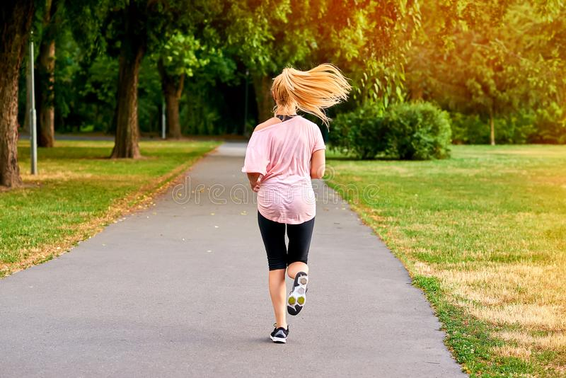 Νέα γυναίκα που τρέχει μακριά στο δρόμο σε ένα πάρκο στοκ εικόνες
