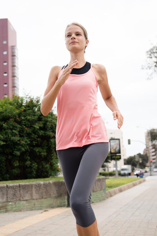 Νέα γυναίκα που τρέχει μετά από ένα ψηλό καφετί κτήριο στοκ φωτογραφίες