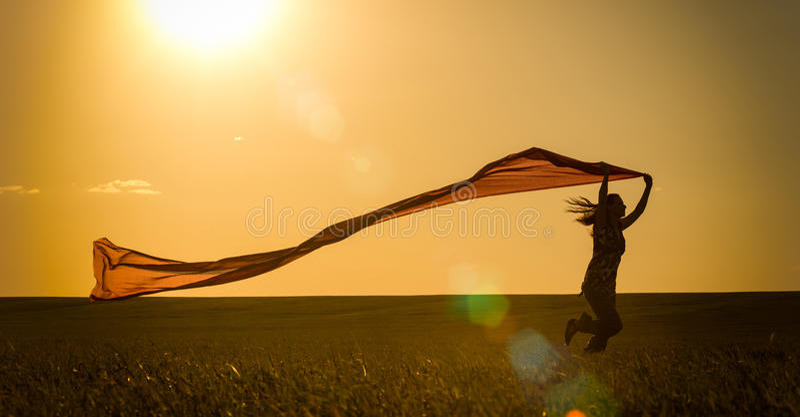 Νέα γυναίκα που τρέχει σε έναν αγροτικό δρόμο στο ηλιοβασίλεμα στο θερινό τομέα Υπόβαθρο αθλητικής ελευθερίας τρόπου ζωής στοκ εικόνα