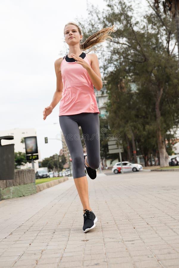 Νέα γυναίκα που τρέχει σε έναν στρωμένο δρόμο στοκ εικόνες