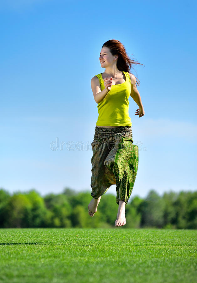 Νέα γυναίκα που τρέχει σε ένα πράσινο λιβάδι στοκ φωτογραφίες με δικαίωμα ελεύθερης χρήσης