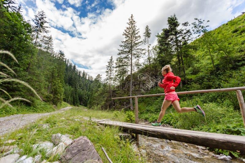 Νέα γυναίκα που τρέχει στη γέφυρα στα βουνά τη θερινή ημέρα στοκ εικόνα με δικαίωμα ελεύθερης χρήσης
