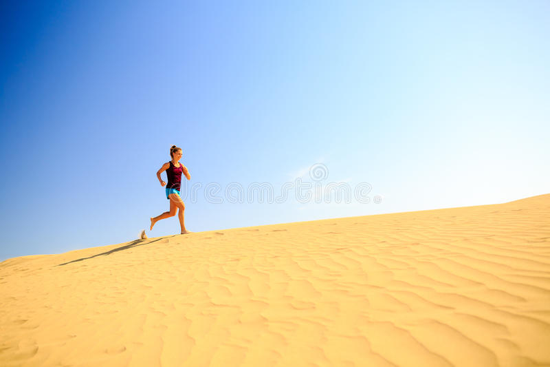 Νέα γυναίκα που τρέχει στους αμμόλοφους ερήμων άμμου στοκ εικόνες