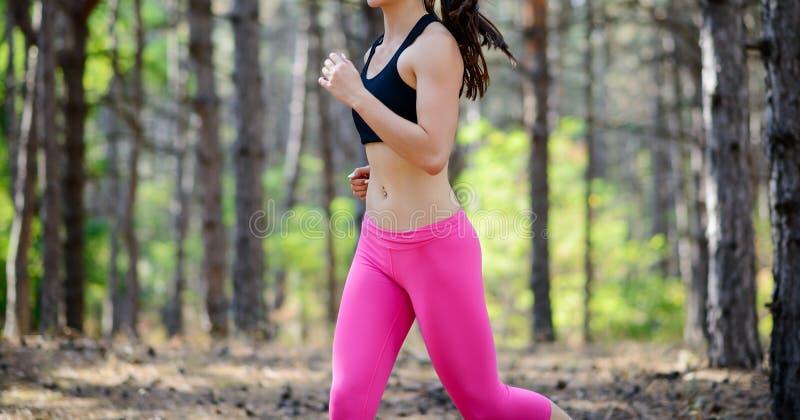 Νέα γυναίκα που τρέχει στο ίχνος στην όμορφη άγρια έννοια τρόπου ζωής πεύκων δασική ενεργό Διάστημα για το κείμενο στοκ φωτογραφίες