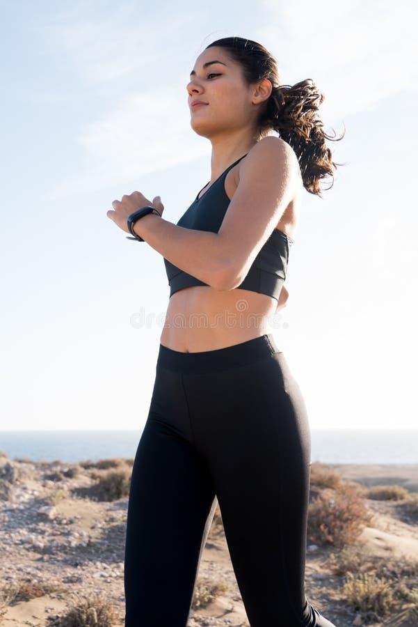 Νέα γυναίκα που τρέχει ως χτυπήματά της στο αεράκι στοκ φωτογραφία