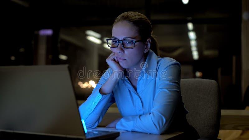 Νέα γυναίκα που τρυπιέται εργασία στον υπολογιστή στην αρχή, εξαντλημένος και unmotivated στοκ φωτογραφίες με δικαίωμα ελεύθερης χρήσης