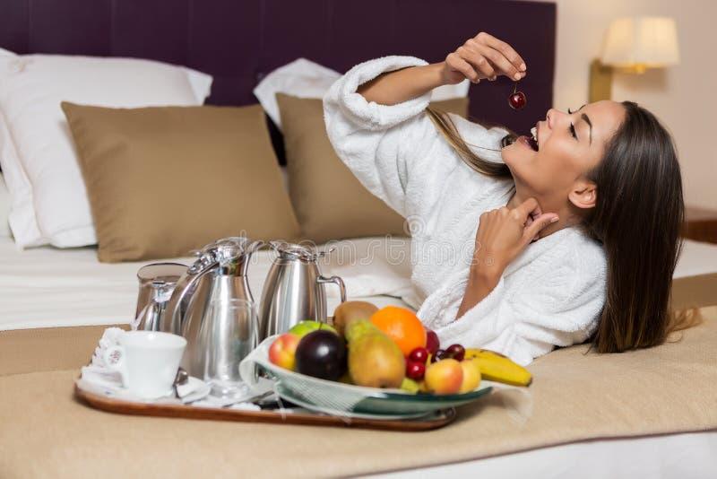 Νέα γυναίκα που τρώει τα φρούτα στο κρεβάτι στοκ φωτογραφίες με δικαίωμα ελεύθερης χρήσης