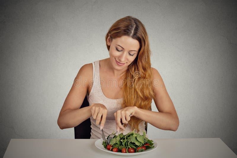 Νέα γυναίκα που τρώει την πράσινη σαλάτα στοκ φωτογραφία με δικαίωμα ελεύθερης χρήσης