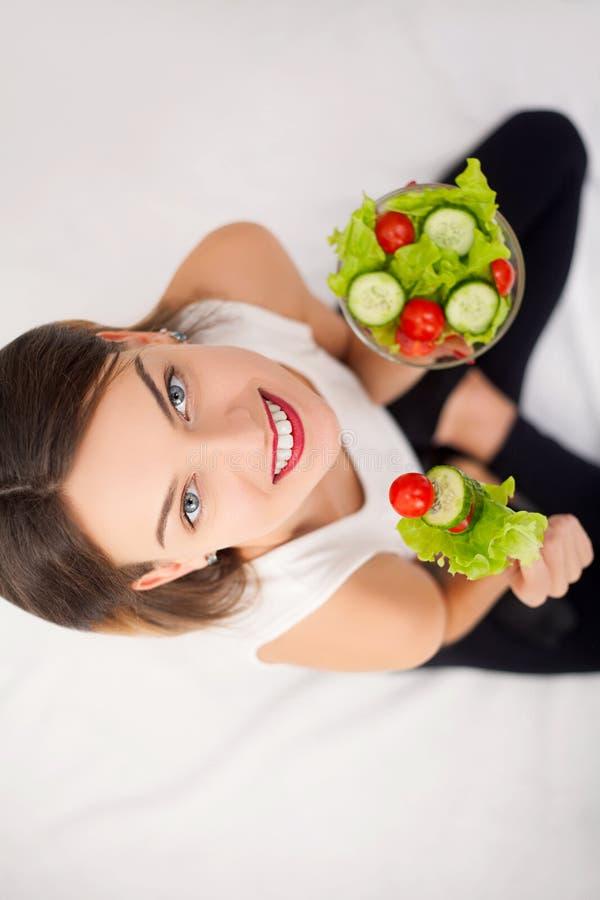Νέα γυναίκα που τρώει την υγιή σαλάτα μετά από το workout στοκ εικόνες
