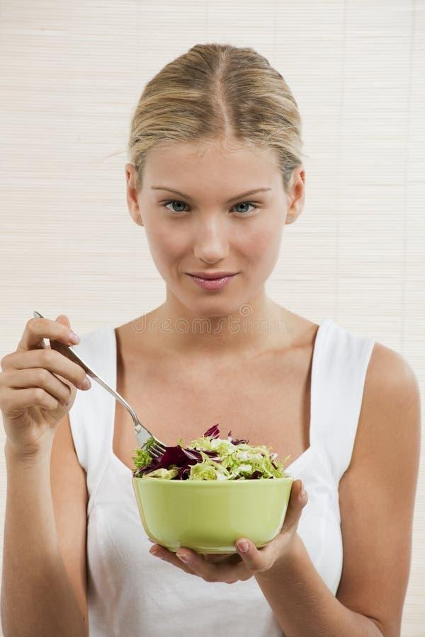 Νέα γυναίκα που τρώει τη φυτική σαλάτα στοκ φωτογραφία με δικαίωμα ελεύθερης χρήσης