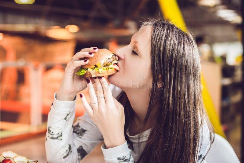Νέα γυναίκα που τρώει τη γυναίκα χάμπουργκερ που τρώει το άχρηστο φαγητό, λιπαρά τρόφιμα στοκ εικόνες