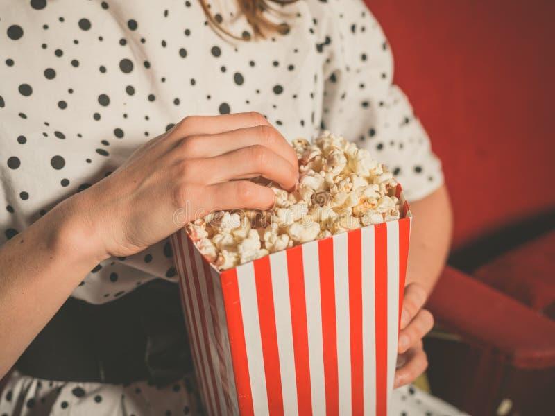 Νέα γυναίκα που τρώει popcorn στη κινηματογραφική αίθουσα στοκ φωτογραφία