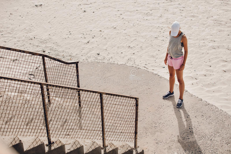 Νέα γυναίκα που υπερασπίζεται μια σκάλα στην παραλία στοκ φωτογραφία