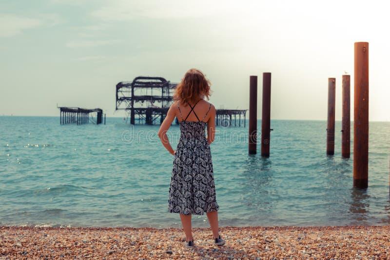 Νέα γυναίκα που υπερασπίζεται τον ωκεανό με την παλαιά αποβάθρα στοκ εικόνα