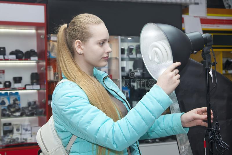 Νέα γυναίκα που φαίνεται επίκεντρα στο κατάστημα phototechnique στοκ φωτογραφία