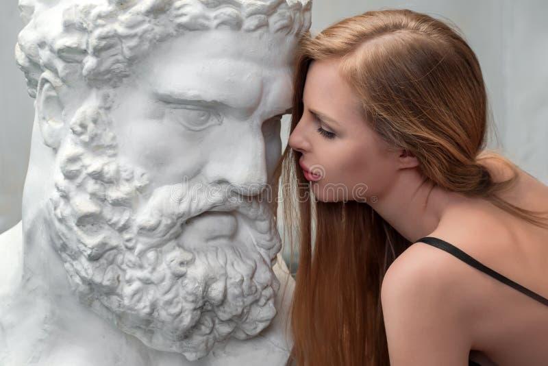Νέα γυναίκα που φιλά το επικεφαλής γλυπτό Heracles, αντίγραφο ασβεστοκονιάματος ενός μαρμάρινου αγάλματος Γιος Zeus, ο Θεός αρχαί στοκ φωτογραφία