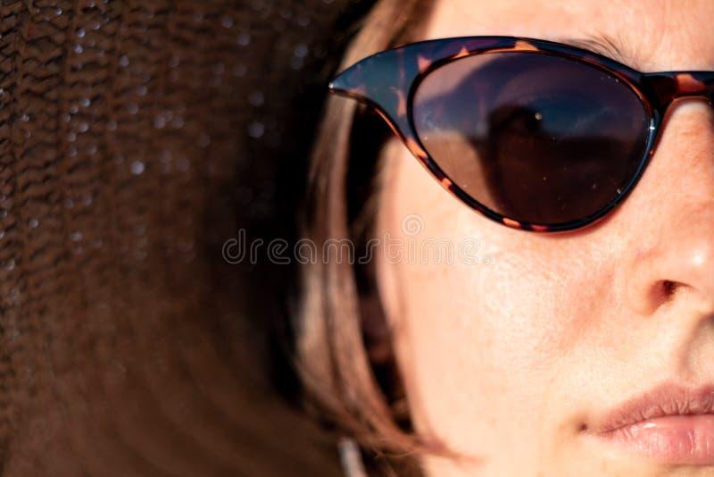 Νέα γυναίκα που φορά ένα θερινό καπέλο και τα γυαλιά ηλίου, πορτρέτο κινηματογραφήσεων σε πρώτο πλάνο στοκ φωτογραφία