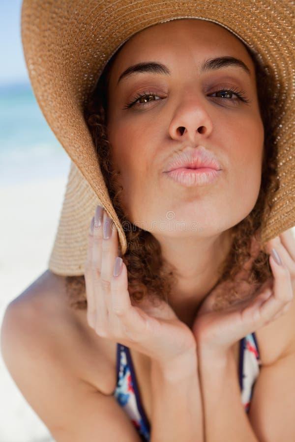Νέα γυναίκα που φορά ένα καπέλο αχύρου puckering τα χείλια της στοκ εικόνες