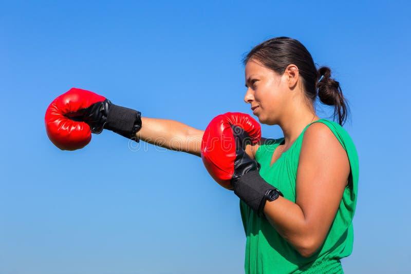 Νέα γυναίκα που φορά τα κόκκινα εγκιβωτίζοντας γάντια με το μπλε ουρανό στοκ εικόνες