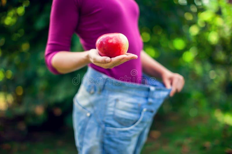 Νέα γυναίκα που φορά τα μεγάλα χαλαρά τζιν με το μήλο διαθέσιμο - βάρος στοκ εικόνες με δικαίωμα ελεύθερης χρήσης