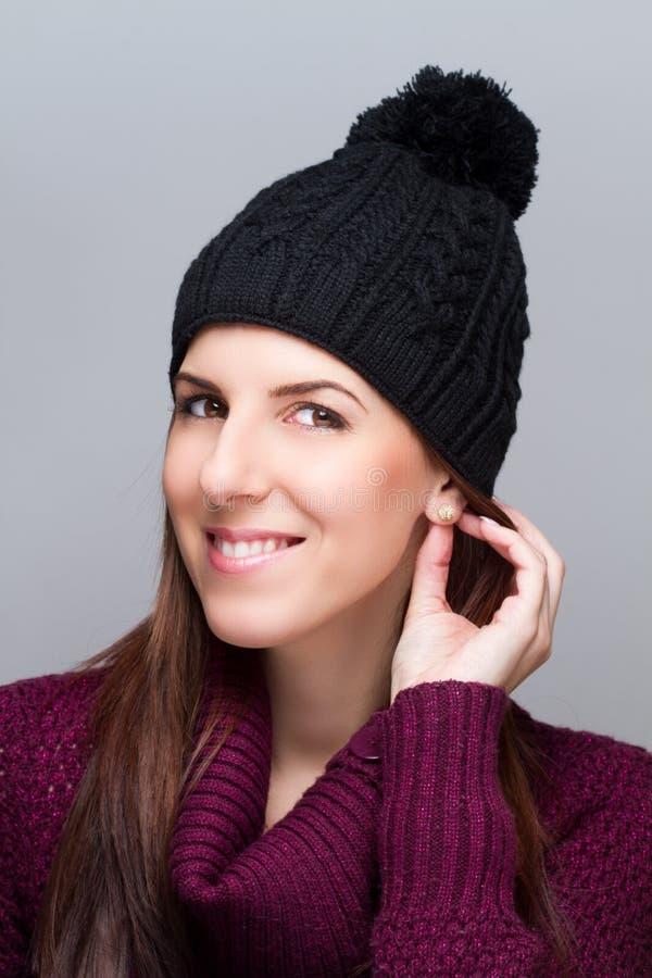 Νέα γυναίκα που φορά την ΚΑΠ και που χαμογελά στο ελαφρύ υπόβαθρο στοκ φωτογραφία με δικαίωμα ελεύθερης χρήσης