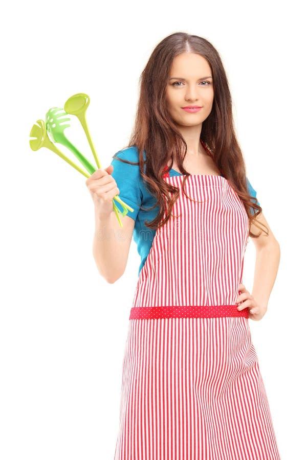 Νέα γυναίκα που φορά την κόκκινη ποδιά και που κρατά τα πλαστικά κουτάλια στοκ φωτογραφία με δικαίωμα ελεύθερης χρήσης