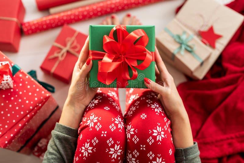 Νέα γυναίκα που φορά τις πυτζάμες Χριστουγέννων που κάθονται στο πάτωμα μεταξύ των τυλιγμένων χριστουγεννιάτικων δώρων, που κρατο στοκ εικόνες