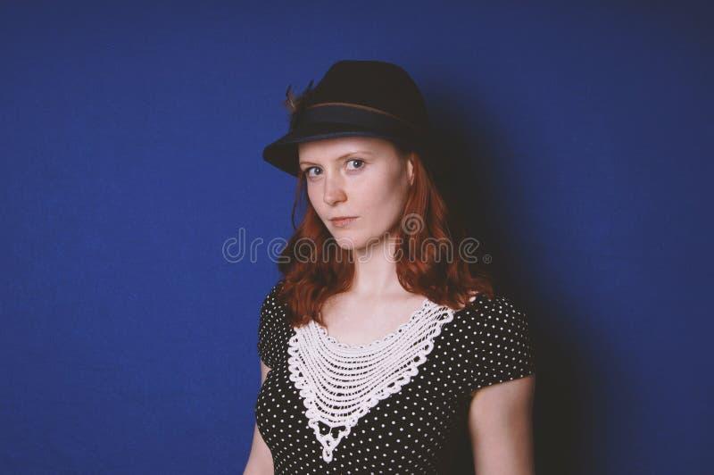 Νέα γυναίκα που φορά το εκλεκτής ποιότητας φόρεμα και το καπέλο στοκ εικόνες