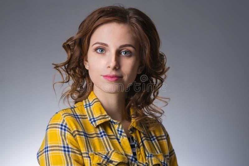 Νέα γυναίκα που φορά το κίτρινο πουκάμισο στο γκρίζο υπόβαθρο στοκ φωτογραφίες