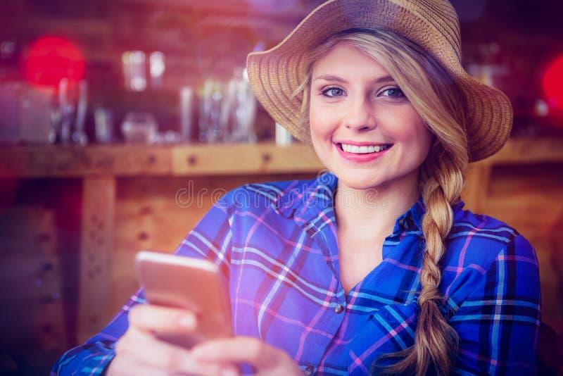Νέα γυναίκα που φορά το καπέλο χρησιμοποιώντας το κινητό τηλέφωνο στον καφέ στοκ εικόνα με δικαίωμα ελεύθερης χρήσης