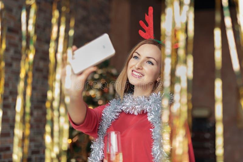Νέα γυναίκα που φορά το κόκκινο φόρεμα με headband ελαφιών ελαφόκερων που παίρνει selfie στη γιορτή Χριστουγέννων στοκ φωτογραφίες με δικαίωμα ελεύθερης χρήσης