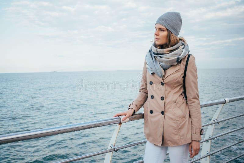 Νέα γυναίκα που φορά το μπεζ παλτό, το μαντίλι, το καπέλο και το σακίδιο πλάτης στοκ εικόνα