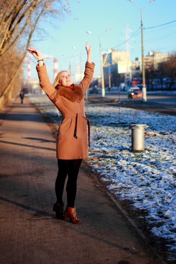 Νέα γυναίκα που φορά το παλτό που περπατά κάτω από την οδό, κρύος χειμώνας DA στοκ φωτογραφίες