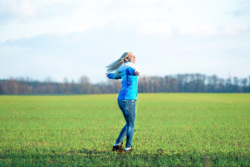 Νέα γυναίκα που χαλαρώνει και που χορεύει στο λιβάδι ελεύθερος χρόνος διασκέδασης στοκ εικόνες