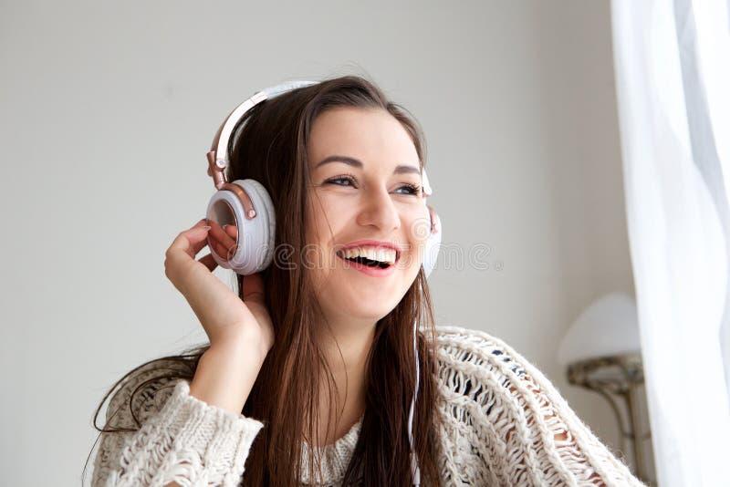 Νέα γυναίκα που χαμογελά και που ακούει τη μουσική με τα ακουστικά στοκ εικόνα