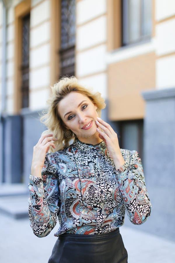 Νέα γυναίκα που χαμογελά και που εξετάζει τη κάμερα έξω στοκ φωτογραφία