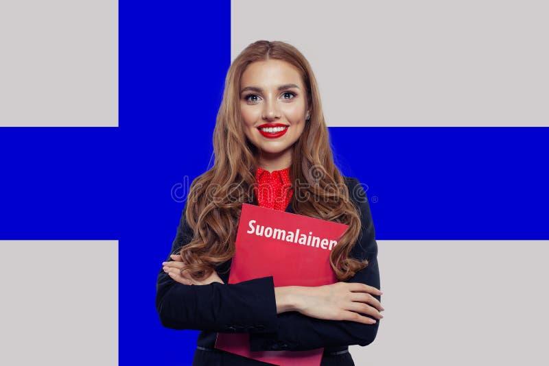 Νέα γυναίκα που χαμογελά και που θέτει ενάντια στη φινλανδική σημαία στοκ φωτογραφίες