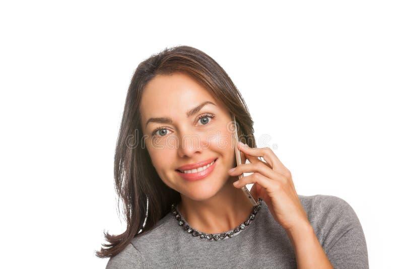 Νέα γυναίκα που χαμογελά και που μιλά στο κινητό τηλέφωνο της που απομονώνεται στοκ εικόνα