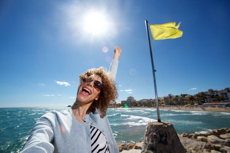 Νέα γυναίκα που χαμογελά με το βραχίονα στον αέρα παίρνοντας selfie στην παραλία στοκ εικόνες