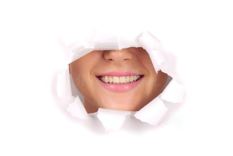Νέα γυναίκα που χαμογελά στην τρύπα στοκ φωτογραφία με δικαίωμα ελεύθερης χρήσης