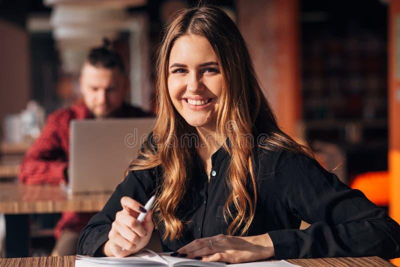 Νέα γυναίκα που χαμογελά στη κάμερα εργαζόμενη μακρινά στη καφετερία Θετικό θηλυκό με το σημειωματάριο στοκ φωτογραφίες