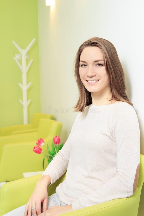 Νέα γυναίκα που χαμογελά στη αίθουσα αναμονής στοκ φωτογραφίες