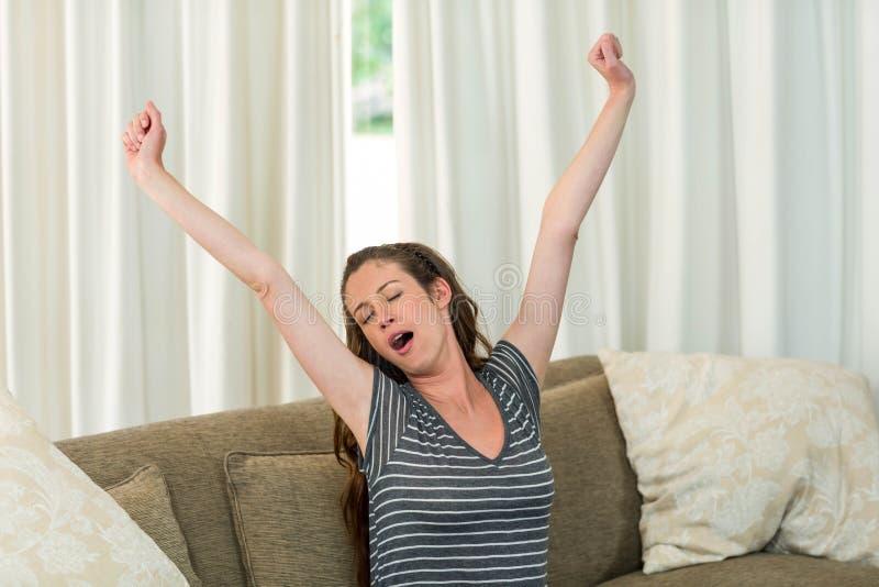 Νέα γυναίκα που χασμουριέται και που τεντώνει τα χέρια της στοκ φωτογραφίες