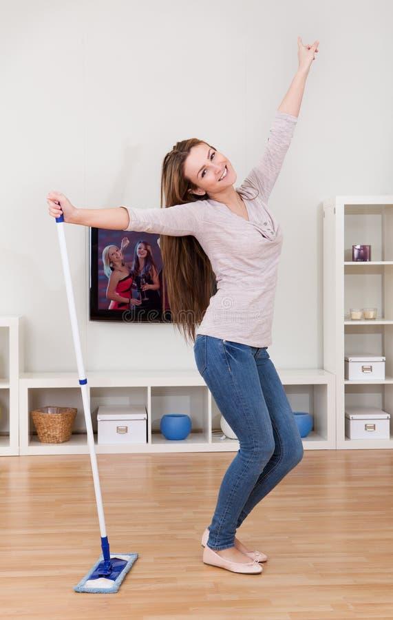 Νέα γυναίκα που χορεύει καθαρίζοντας το πάτωμα στοκ φωτογραφία