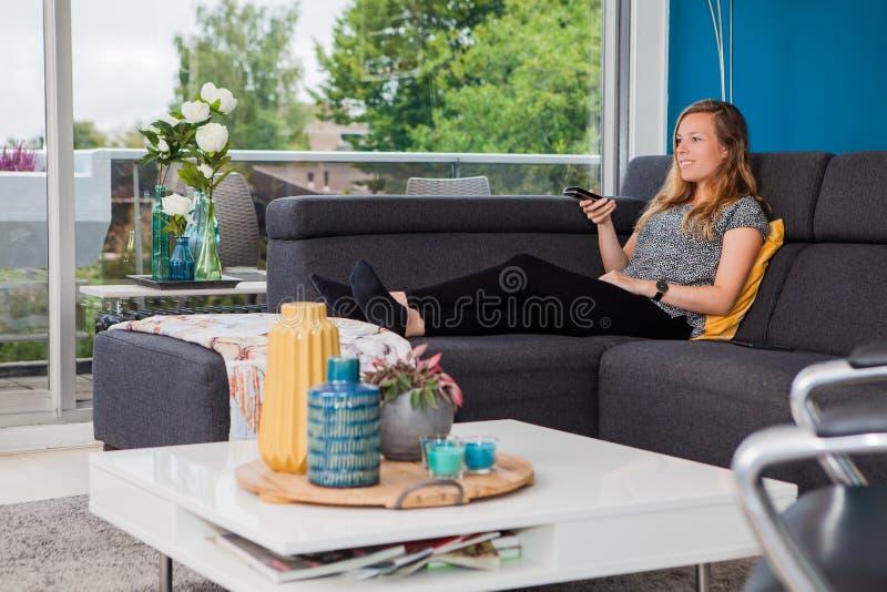 Νέα γυναίκα που χρησιμοποιεί έναν τηλεχειρισμό σχετικά με τον καναπέ στοκ φωτογραφία με δικαίωμα ελεύθερης χρήσης