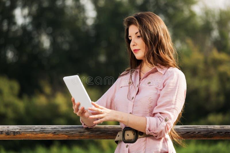 Νέα γυναίκα που χρησιμοποιεί έναν ψηφιακό υπολογιστή ταμπλετών στοκ εικόνα με δικαίωμα ελεύθερης χρήσης